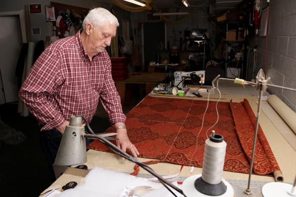 Frank cutting upholstery fabric for a cat mat