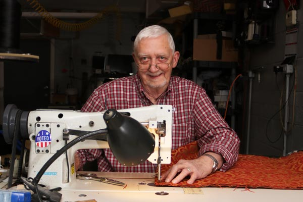 Frank at his sewing machine with upholstery fabric for a cat mat